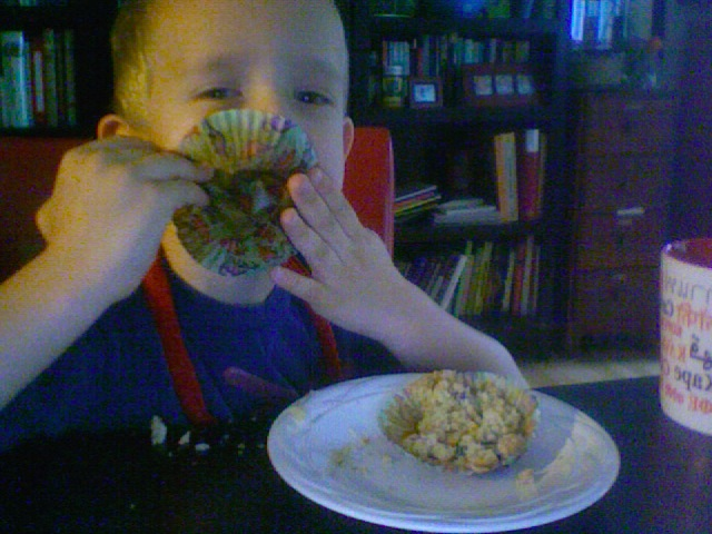 Logan, still in his apron, tryin to eat every last Oatmeal-Raisin Muffin crumb off the Dinosaur wrapper.
